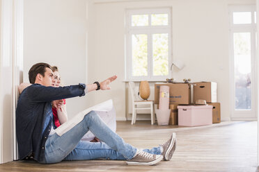 Young couple in new home sitting on floor discussing ground plan - UUF10744