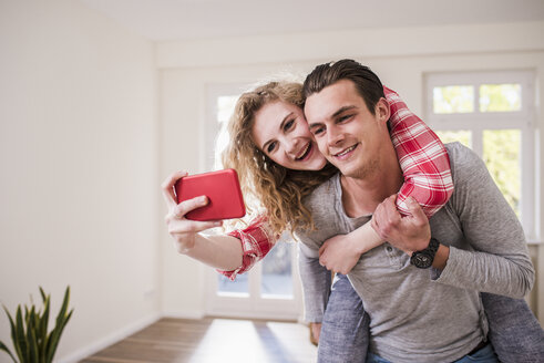 Happy young couple in new home taking a selfie - UUF10750
