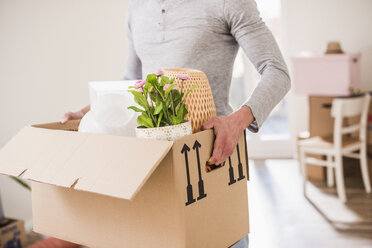 Young man carrying cardboard box in new home - UUF10753