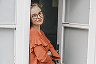 Portrait of confident young woman leaning against door - KNSF01491