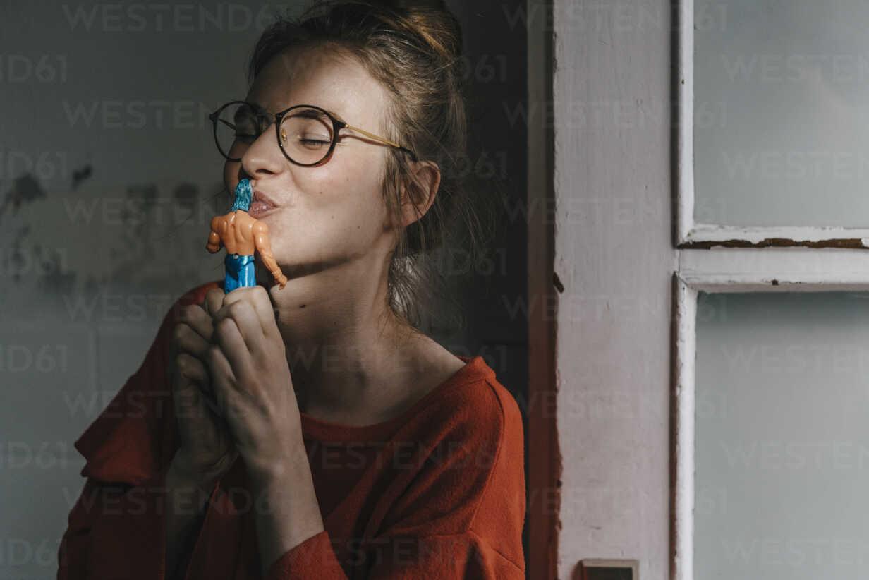 Young woman kissing superhero comic figurine - KNSF01494 - Kniel Synnatzschke/Westend61