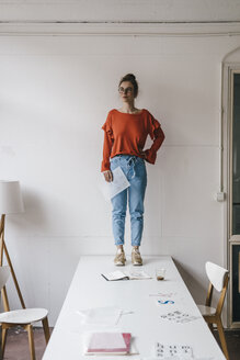 Young woman standing on table thinking - KNSF01500