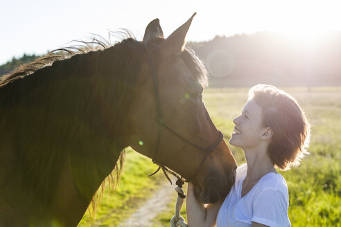 Profiles of young woman and horse at backlight - TCF05424