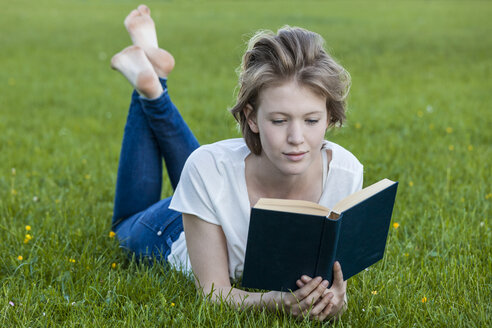 Barefoot young woman lying on a meadow reading a book - TCF05427