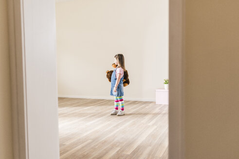 Girl in empty apartment holding teddy - UUF10758