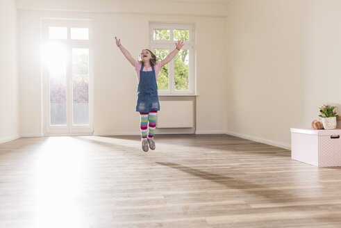 Happy girl jumping in empty apartment - UUF10761