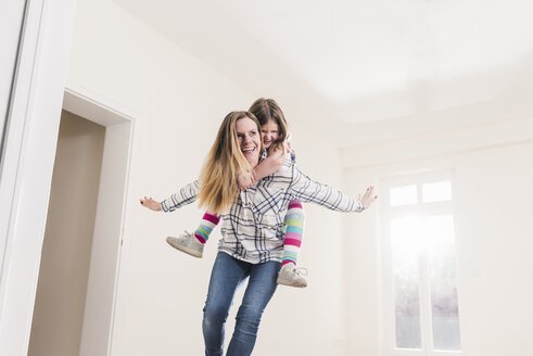 Happy mother and daughter in empty apartment - UUF10770