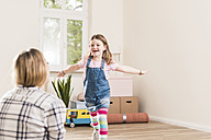 Happy girl running towards mother in empty apartment - UUF10773
