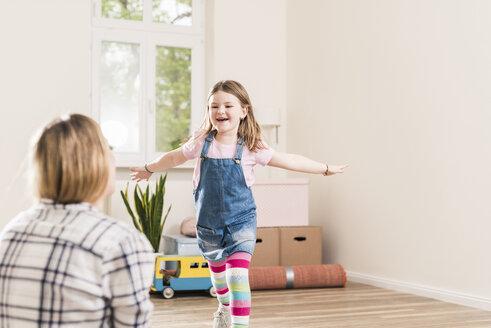 Happy girl running towards mother in empty apartment - UUF10773
