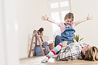 Happy mother and daughter playing in new home - UUF10779