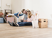 Parents and daughter using tablet in new home - UUF10782