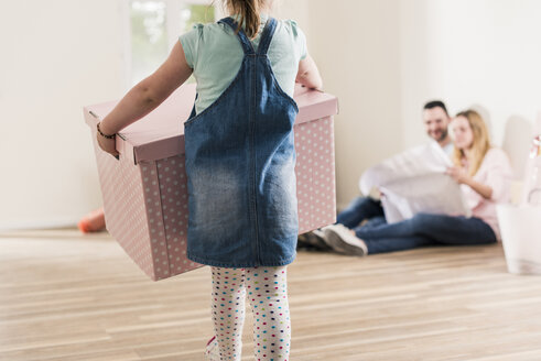 Girl carrying cardboard box in empty apartment with parents in background - UUF10785