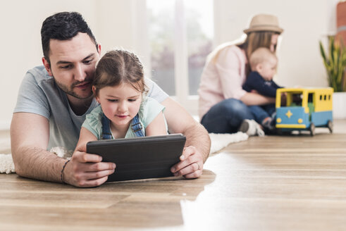 Father and daughter using tablet in new home with woman and baby in background - UUF10788