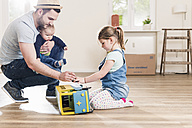Father playing with two children in new home - UUF10791