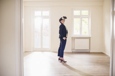 Woman in empty apartment wearing VR glasses - UUF10800