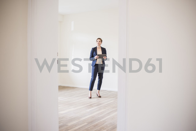 Woman in empty apartment with tablet - UUF10803