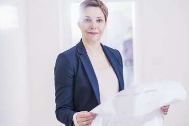 Portrait of confident real estate agent holding plan - UUF10806