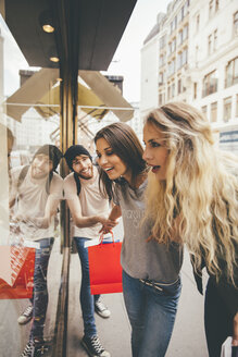 Young women looking fascinated in shop window, boyfriend trying to pull her away - AIF00432