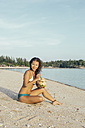 Smiling woman sitting on the beach with beverage - MOMF00170