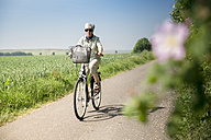 Germany, Senior woman riding bicycle in summer - FRF00515