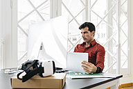 Businessman working in office, reading papers - JRFF01333