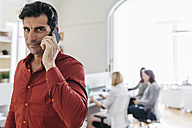 Businessman talking on the phone in office with colleagues working in background - JRFF01348