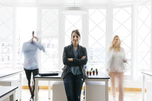 Young businesswoman standing with arms crossed in office while colleagues are moving - JRFF01360
