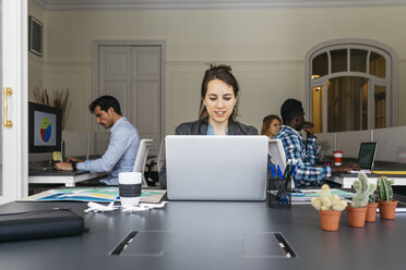 Young businesswoman using laptop, colleagues working in background - JRFF01366