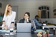 Young businesswomen working together, using laptop, colleague sitting in background - JRFF01369