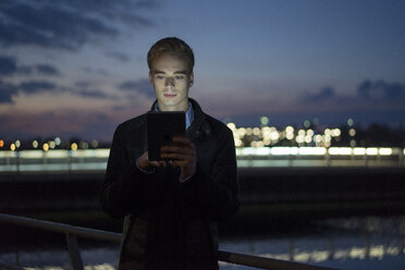 Portrait of young man using tablet outdoors at twilight - JOSF01046