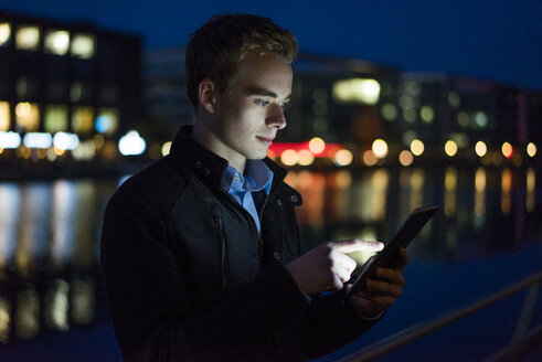 Young man using tablet outdoors at night - JOSF01055