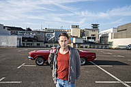 Portrait of mature man in front of his sports car on parking level - FMKF04158