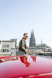 Germany, Cologne, portrait of smiling mature man with his parked sports car - FMKF04167