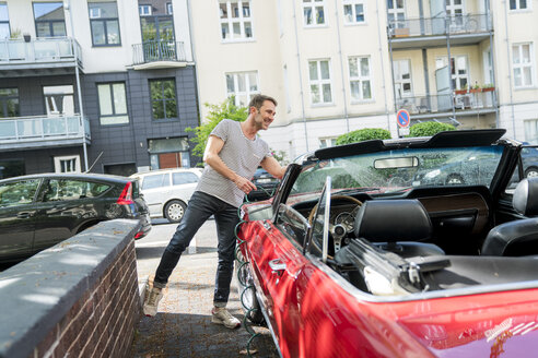 Smiling mature man washing his sports car - FMKF04170