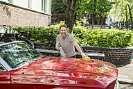 Smiling mature man washing his sports car - FMKF04173