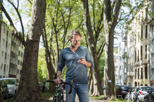 Smiling mature man with bicycle in the city looking at cell phone - FMKF04188