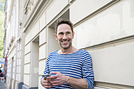 Portrait of smiling with smartphone leaning against facade - FMKF04194