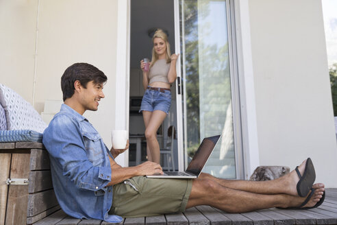 Man sitting on terrace using laptop with woman in background - WESTF23172