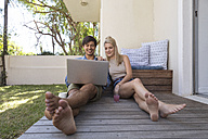 Smiling young couple sitting on terrace using laptop - WESTF23175