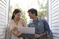 Smiling young couple sitting on windowsill sharing tablet - WESTF23196