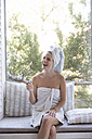 Laughing young woman wrapped in a towel holding toothbrush - WESTF23199