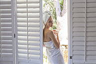 Young woman wrapped in a towel holding cup of coffee - WESTF23205