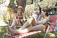 Two happy young women in garden sharing cell phone - WESTF23232