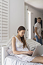 Young woman using laptop in bedroom with man in background - WESTF23247
