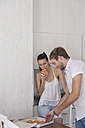 Young couple eating pizza in kitchen - WESTF23259