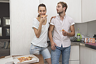 Young couple eating pizza in kitchen - WESTF23262