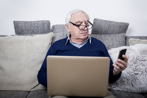 Senior man sitting on couch, using laptop and smartphone - WESTF23298