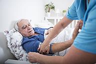 Gereatric nurse measuring blood pressure of patient, lying in bed - WESTF23352