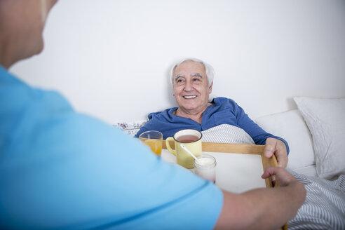 Gereatric nurse bringing tea at patient's bed - WESTF23355