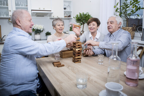 Group of seniors having a games evening at home - WESTF23364
